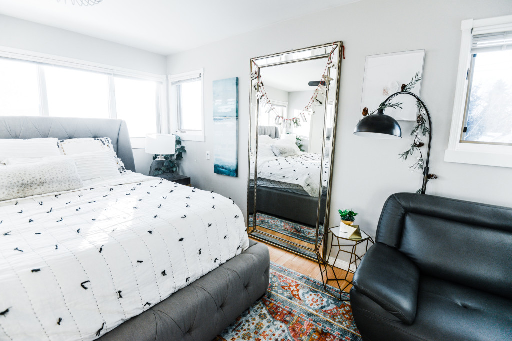 holiday bedroom light bright airy modern grey linen bed frame colourful rug. Large mirror. Tassel embroiled bed quilt