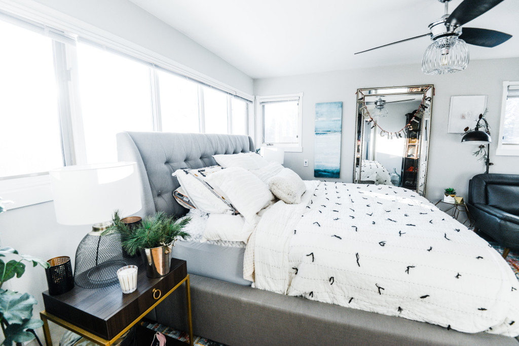 holiday bedroom light bright airy modern grey linen bed frame colourful rug. Large mirror. Tassel embroiled bed quilt  Grey leather chair gold geometric side table